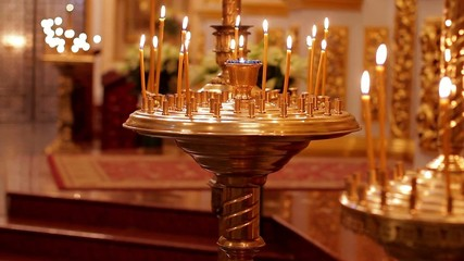 Candles are lit on the candlesticks in the cathedral.