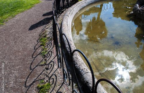 Leinwanddruck Bild fontana con riflesso del sole nell'acqua