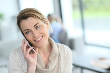 Portrait of mature blond woman talking on phone