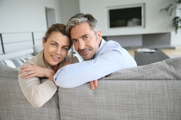 Portrait of cheerful mature couple sitting in sofa