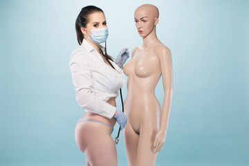 Sexy Female Nurse Standing Besides a Human Dummy