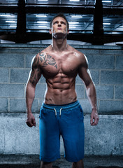 Handsome Athletic Young Man with Tattoo Looking Up