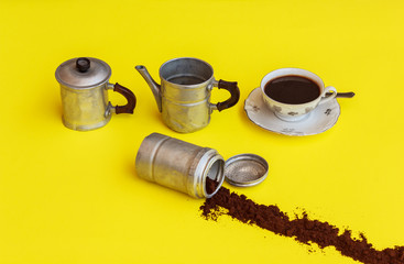 the components  of a coffee maker with alongside  the cup full o
