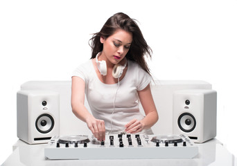 Trendy sexy DJ dressed in white mixing music