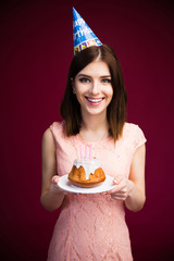 Smiling woman holding cake with candles
