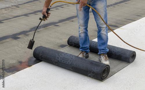 Leinwanddruck Bild Worker preparing part of bitumen roofing felt roll