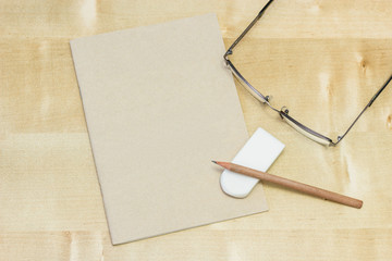 pencil and rubber on note book with grasses.