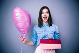 Amazed woman holding balloon and gift box
