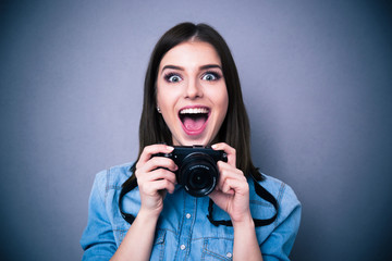Cheerful young woman holding camera