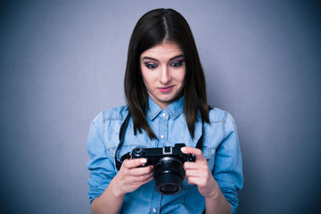 Surprised young woman looking on camera screen