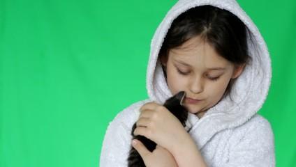 cute little girl in white bathrobe is holding a kitten