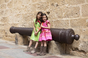 Niñas con vestidos de colores junto a cañón