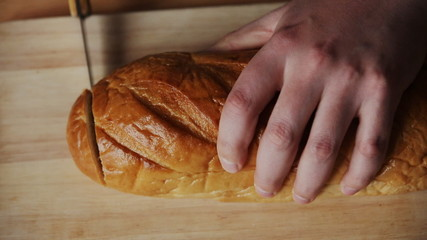 the guy in the kitchen slicing a loaf