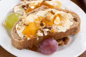 bread with butter, honey, nuts and grapes