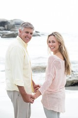 Happy couple holding hands and smiling at camera