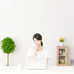 パソコンの前に座って迷う女性