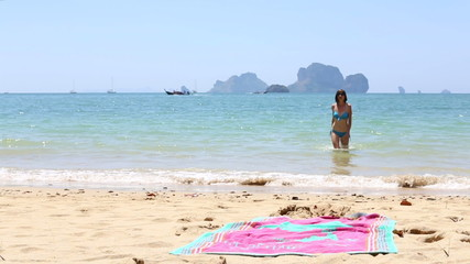 young girl comes out of sea lies down on beach towel