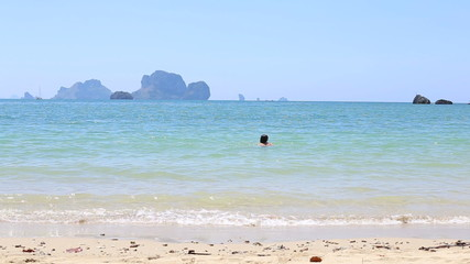 brunette girl swims in sea against rocky islands