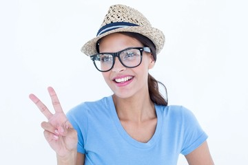 Smiling woman making peace and love gesture