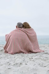 Happy couple sitting on the sand with blanket around them