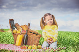 Beautiful little girl smiling doing a picnic on the green spring