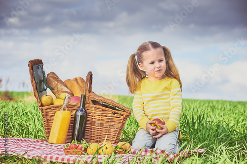 Beautiful little girl smiling doing a picnic on the green spring - 81226291