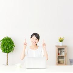 パソコンの前に座って指差す女性