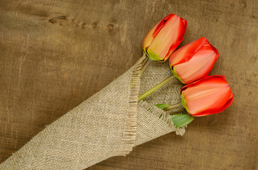 bouquet of red tulips on burlap background