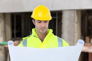 Composite image of architect analyzing blueprint