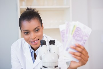 Smiling scientist holding money and looking at camera