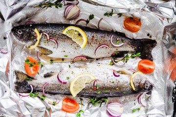two raw river trouts with thyme, lemo, red onion in foil closeup