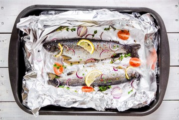two raw rainbow trouts with thyme, lemon, red onion in foil