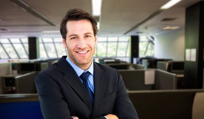 Composite image of smiling businessman with arms crossed