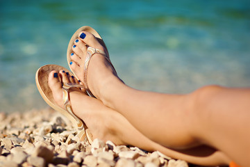 womans legs foot at beach in summer
