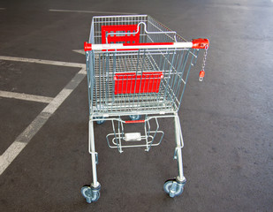 metal trolley shopping basket at asphalt background