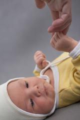 Newborn baby touching mothers hand