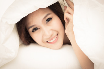 Pretty young woman in bed under the white bed sheet