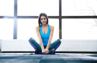 Young beautiful woman sitting on yoga mat