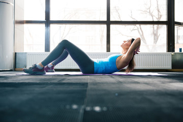 Young woman lying on the yoga mat and doing fitness exercise