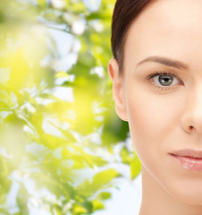 young woman face over green leaves background