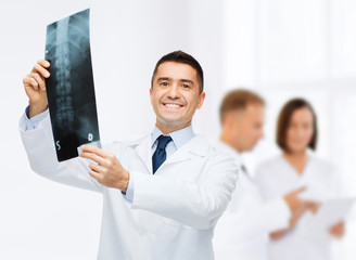 smiling male doctor holding x-ray at hospital