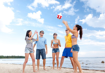 group of happy friends playing beach ball
