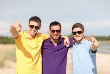 smiling friends in sunglasses showing thumbs up