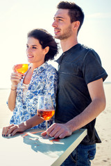 Couple relaxing while having spritz in a seafront