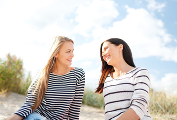 happy teenage girls or young women on beach