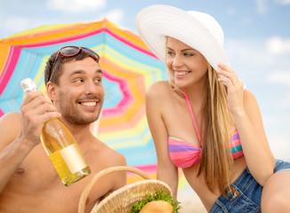 chappy ouple having picnic and sunbathing on beach