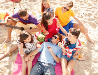 group of happy friends having fun on beach