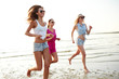 group of smiling women running on beach