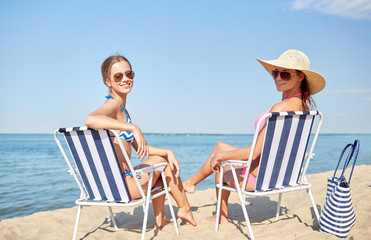 happy women sunbathing in lounges on beach