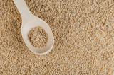 Unpolished brown rice texture with wooden spoon poster